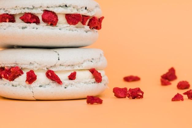 色付きの背景に乾燥した赤い果実と白いマカロンの詳細 無料写真