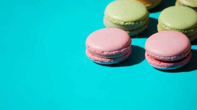 ターコイズブルーの背景にピンクとグリーンのマカロン 無料写真