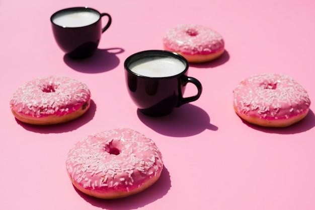 Черная чашка кофе с пончиками на розовом фоне Бесплатные Фотографии
