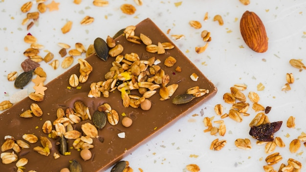 オーツ麦とドライフルーツの白い背景に対してチョコレートバー 無料写真