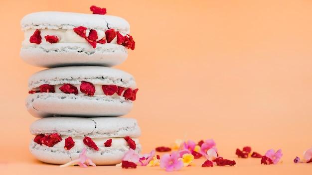 ベージュ色の背景上の花とマカロンの積み上げ 無料写真