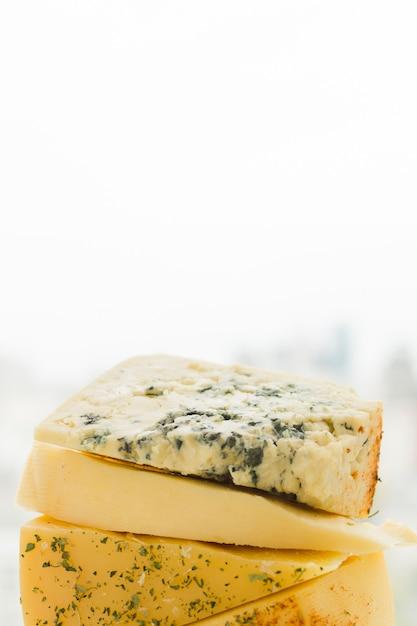 Сложены треугольные ломтики сыра на белом фоне Бесплатные Фотографии