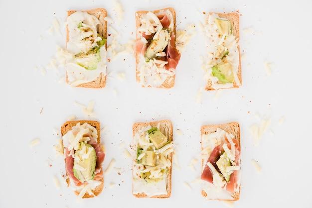 おろしたチーズとパンをトーストします。白い背景の上にハムとアボカドのスライス 無料写真