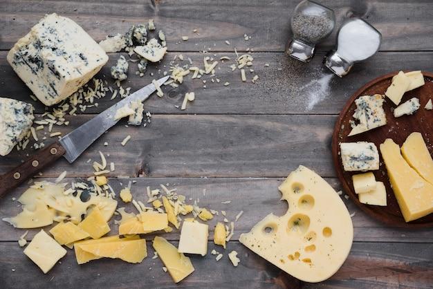 Вид сверху шейкер с солью и перцем с сыром на деревянный стол Бесплатные Фотографии
