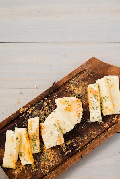 Травы и специи на ломтики сыра над деревянным столом Бесплатные Фотографии