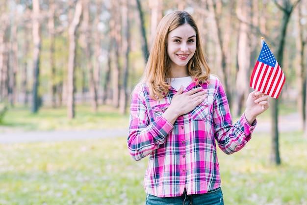 Женщина с флагом сша стоит в парке Бесплатные Фотографии