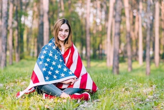 アメリカの国旗を包む地面に座っている若い女性 無料写真