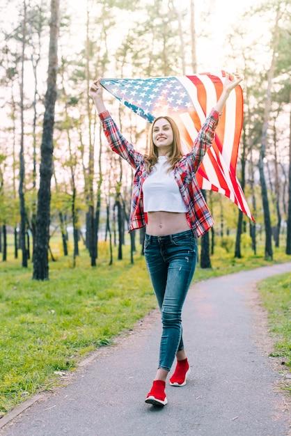 Веселая молодая женщина с флагом сша Бесплатные Фотографии