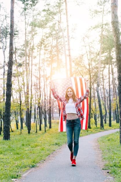 Студентка с флагом сша в лучах солнца Бесплатные Фотографии