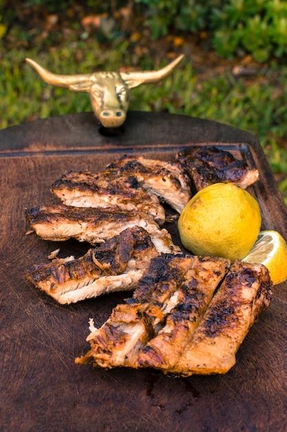 カット肉のグリルとテーブルの上のレモンスライス 無料写真