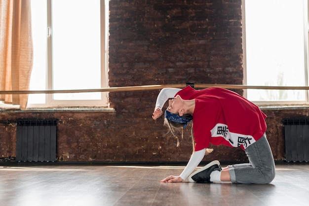 ダンススタジオで練習をしている女性ダンサーの側面図 無料写真