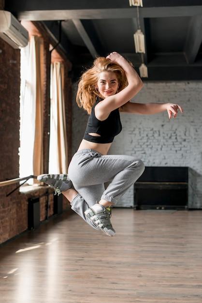 空気中のジャンプ笑顔金髪の若い女性の肖像画 無料写真