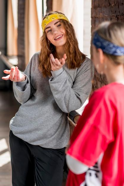 彼女の友達と話している笑顔の若い女性 無料写真