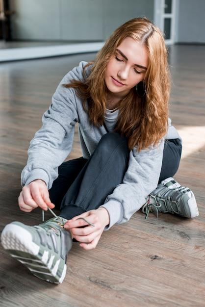 堅木張りの床の靴ひもを結ぶことに座っている金髪の若い女性 無料写真