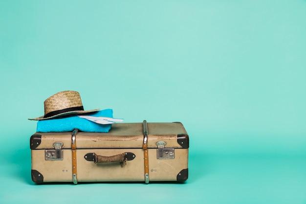 帽子の紙とそれの上に布で茶色のスーツケース 無料写真
