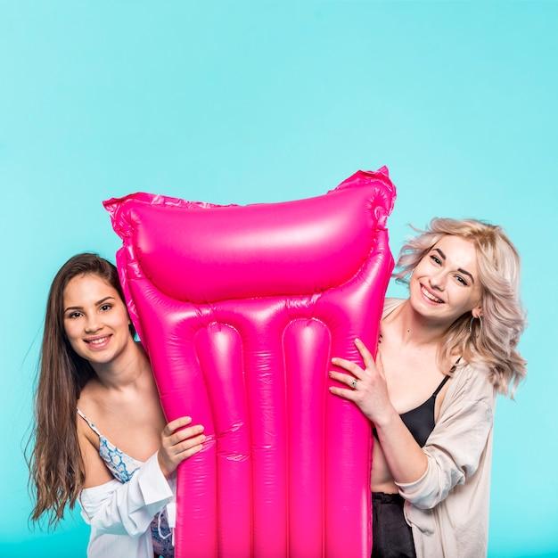 明るいピンクのプールエアーマットを持つ女性 無料写真