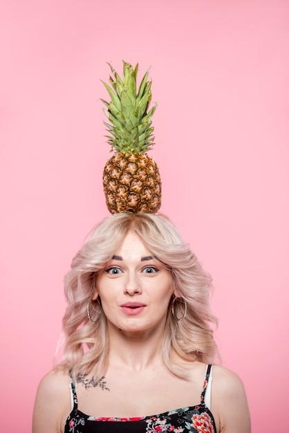 頭の上のパイナップルと驚いた女性 無料写真