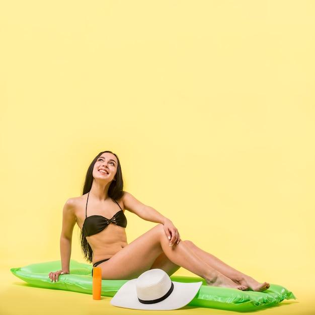 水のマットレスの上に座って、笑顔の黒い水着の女性 無料写真