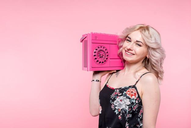 肩にテープレコーダーを持つ女性 無料写真