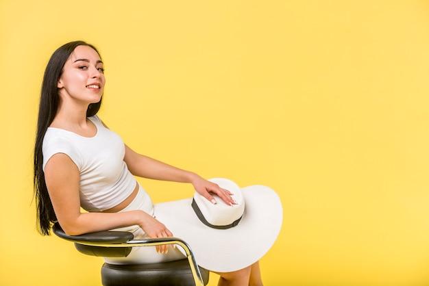 椅子に座ってエレガントな若い女性 無料写真