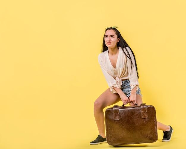 若い女性ドラッグビンテージスーツケース 無料写真