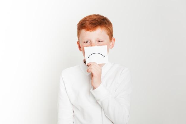 Рыжий мальчик держит карту с грустным лицом Бесплатные Фотографии