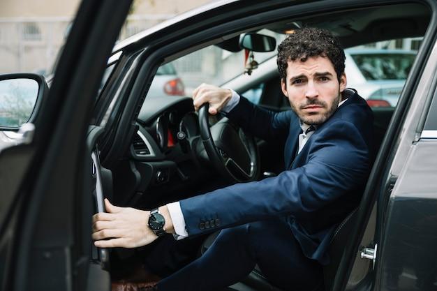 現代のビジネスマンが車の中で座っています。 無料写真