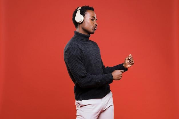黒い男の子がヘッドフォンでポーズ 無料写真