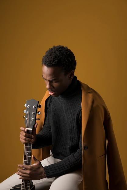 黒い男の子がギターを弾く 無料写真