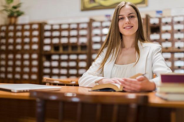 図書館で勉強している女性と学校のコンセプトに戻る 無料写真