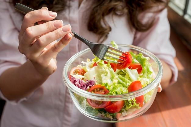 ブルネットの女性、サラダを食べる 無料写真