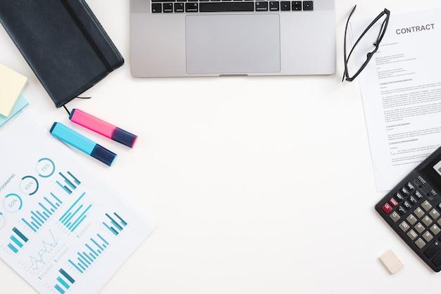 ノートパソコンとアナリティクスを備えたオフィスデスクトップ 無料写真