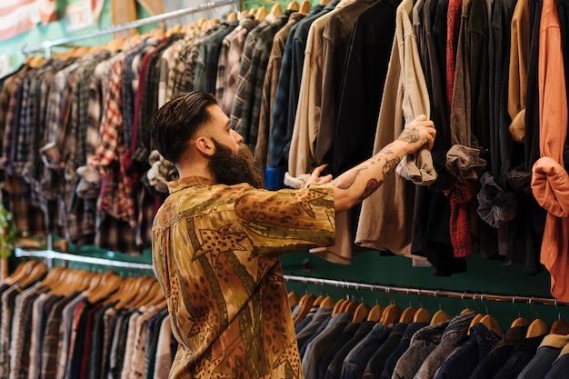 衣料品店の中のレールに掛かっているシャツを見て若い男 無料写真