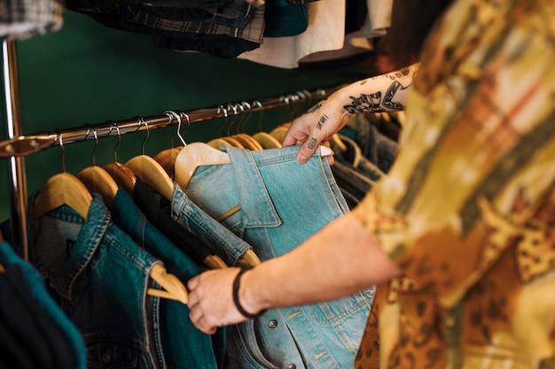 衣料品店でレールに掛かっている青いジャケットを選ぶ人間の手のクローズアップ 無料写真