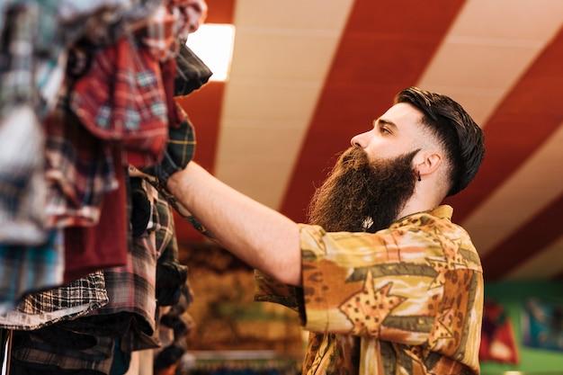 店のレールに掛かっている服を見て長いひげを生やした男 無料写真