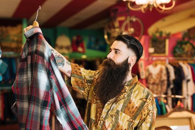 おしゃれな若い男が店で服を買いに 無料写真
