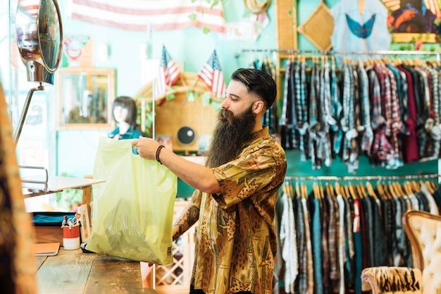 Молодой человек, держащий пластиковый пакет в бутике Бесплатные Фотографии