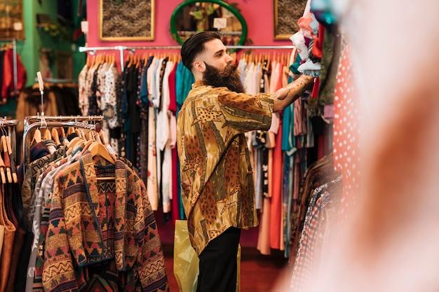 店のレールにぶら下がっている服を見て男の側面図 無料写真