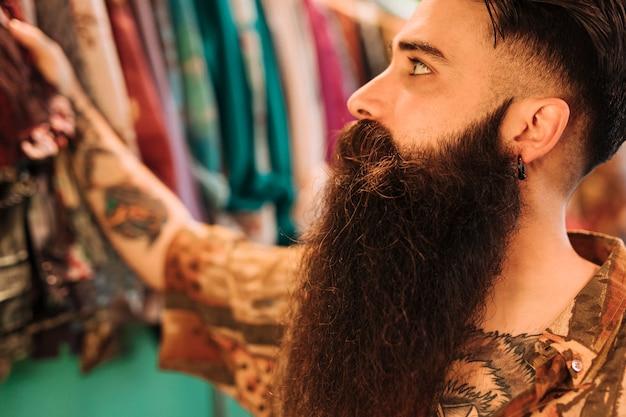ハンサムなひげを生やした男の洋服店でのショッピング 無料写真
