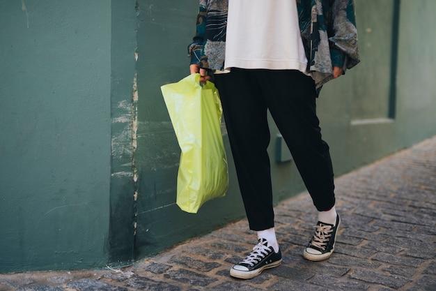 緑のキャリーバッグを手に保持している壁の近くに立っている人の低いセクション 無料写真