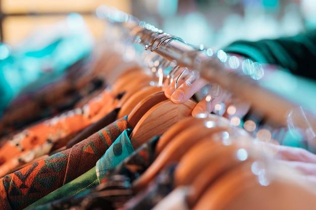 Рука мертвеца выбирая цветочную рубашку на вешалке, висящей на рельсе Бесплатные Фотографии