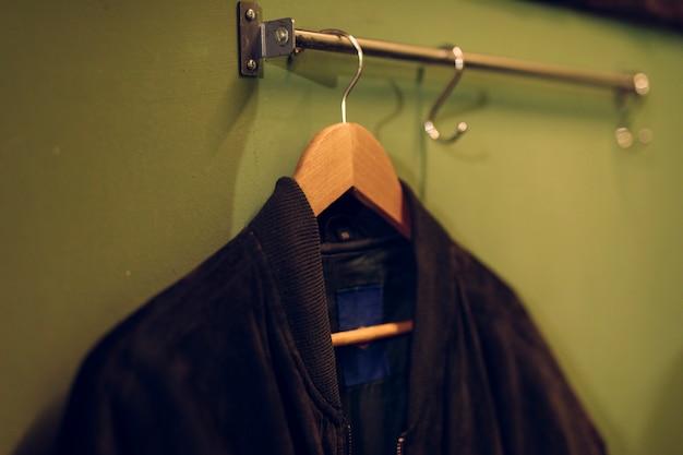 壁にレールに掛かっている木製ハンガーに黒いジャケット 無料写真