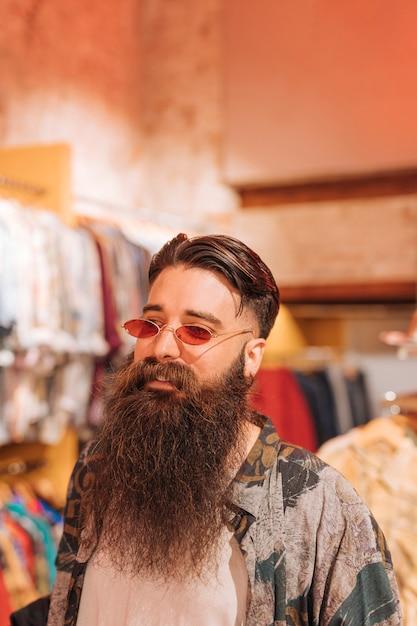 衣料品店に立っているサングラスをかけているひげを生やした若い男のクローズアップ 無料写真