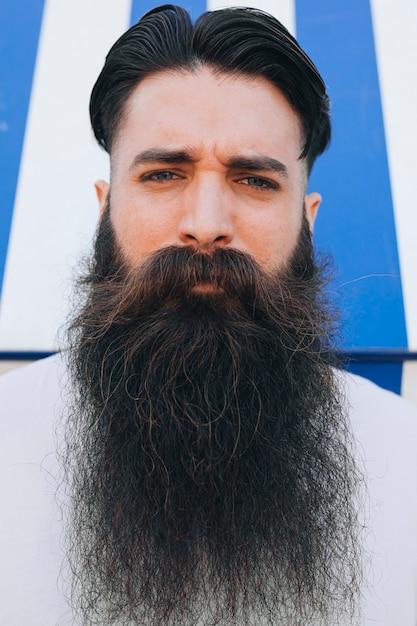 カメラを見て長いひげを持つハンサムな若い男の肖像 無料写真