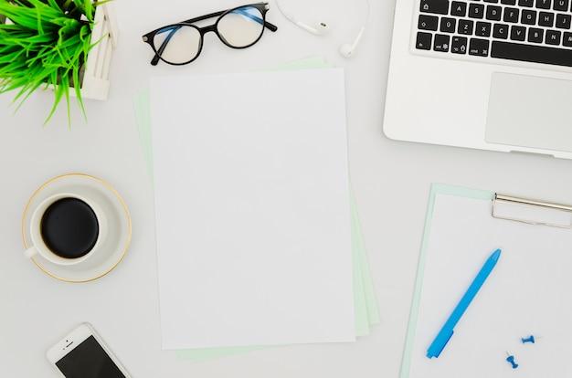 ノートパソコンの横にあるフラットレイ紙モックアップ 無料写真