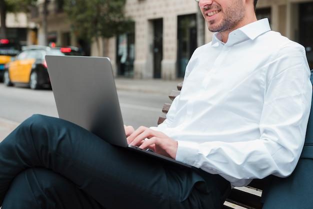 ラップトップを使用してベンチに座っている笑顔の青年実業家 無料写真