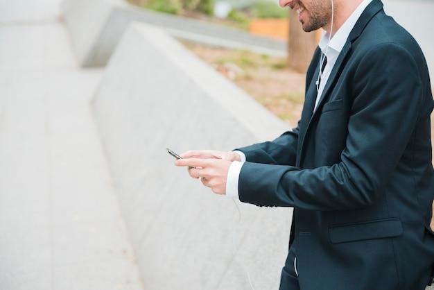スマートフォンを使用して青年実業家の肖像画を笑顔 無料写真