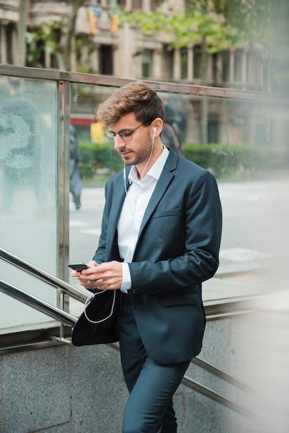 Вид сбоку бизнесмена с помощью мобильного телефона с его наушниками в ушах Бесплатные Фотографии
