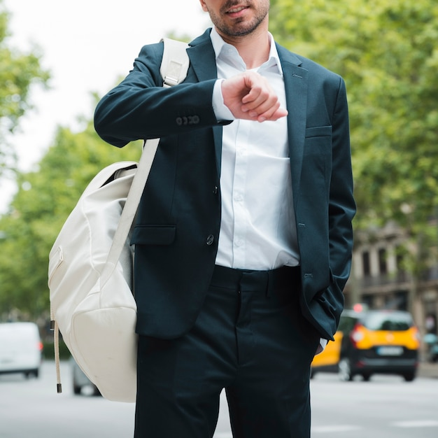路上で時間を見ている彼の肩に白いバックパックを持ったビジネスマンのクローズアップ 無料写真