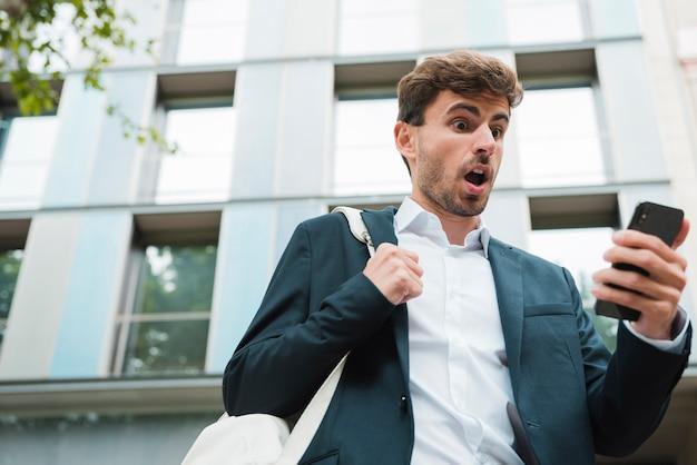 携帯電話を見て彼のバックパックとショックを受けた青年実業家 無料写真